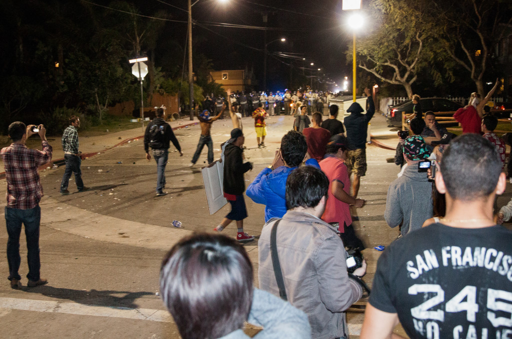 A crowd forms in front of a line of police on Del Playa Drive. Benjamin Pu/Daily Nexus