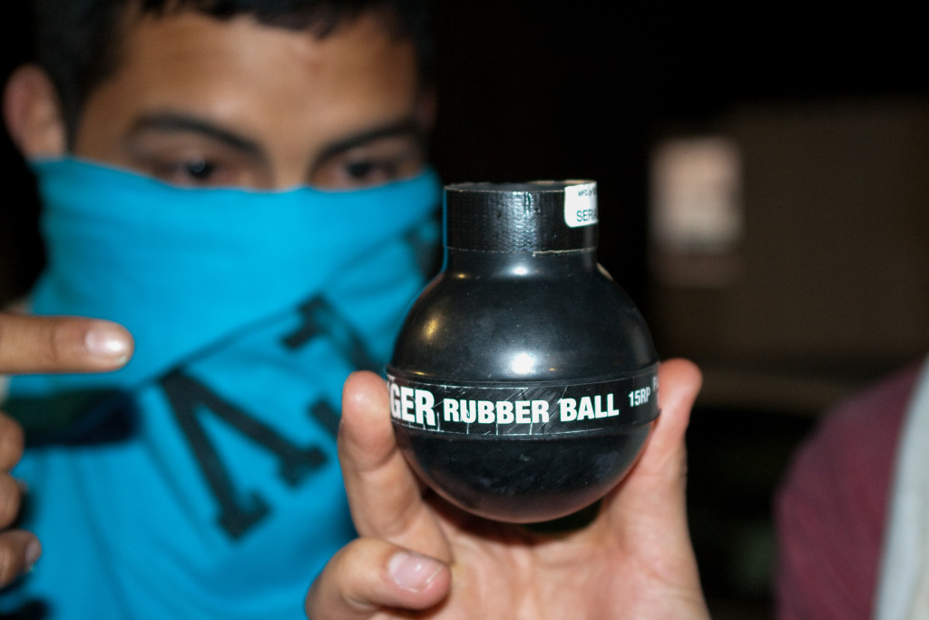 An Isla Vista resident--who has his face covered due to the deployment of tear gas--shows the size of the rubber bullets used by police to neutralize the rioters. Robert Johnson/Daily Nexus