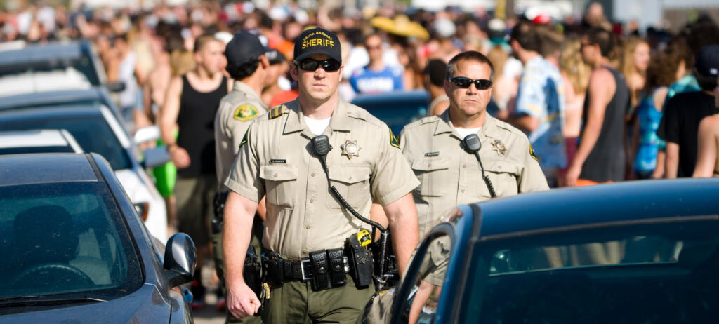 Local law enforcement observe crowds of party-goers parading the streets of Isla Vista during last year's Deltopia celebration.