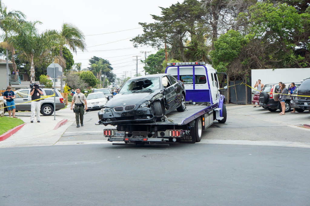 Law enforcement remove Elliot Rodger's black BMW from Del Playa Drive Saturday afternoon. Rodger collided with a parked vehicle after slaughtering six individuals.  (John Clow / Daily Nexus)