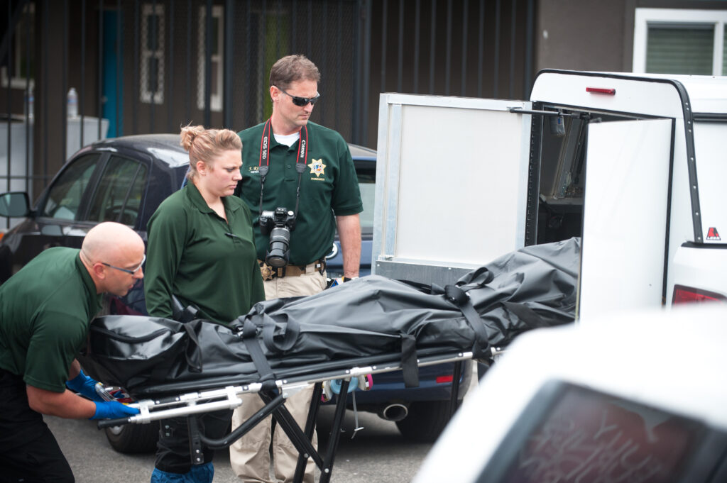 Law enforcement removes a dead body from the apartment of Elliot Rodgers late Saturday afternoon. Rodgers stabbed three victims in his building before murdering another three and injuring 13 in drive-by shootings. (Kenneth Song / Daily Nexus)