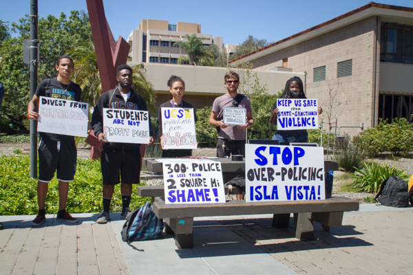 """Students expressed dissatisfaction with Santa Barbara County Sheriff Department's """"Keep isla Vista Safe"""" Campaign with signs, marching around the UCSB Arbor.  Brendan Mansfield/Daily Nexus"""
