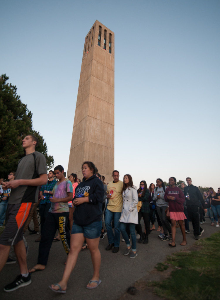 UCSB students and vigil attendees solemnly walk past Storke Tower as they make their way to People's Park in Isla Vista.