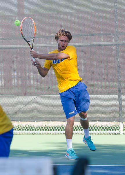 Playing in a singles match against his own teammate, Teague Hamilton hits the ball over the net. Christina DeMarzo/Daily Nexus