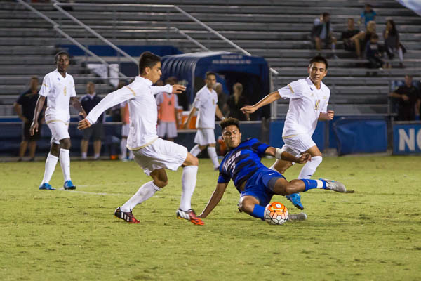 With his opponent fast approaching, Randy Mendoza slides to get the ball. Dustin Harris/Daily Nexus