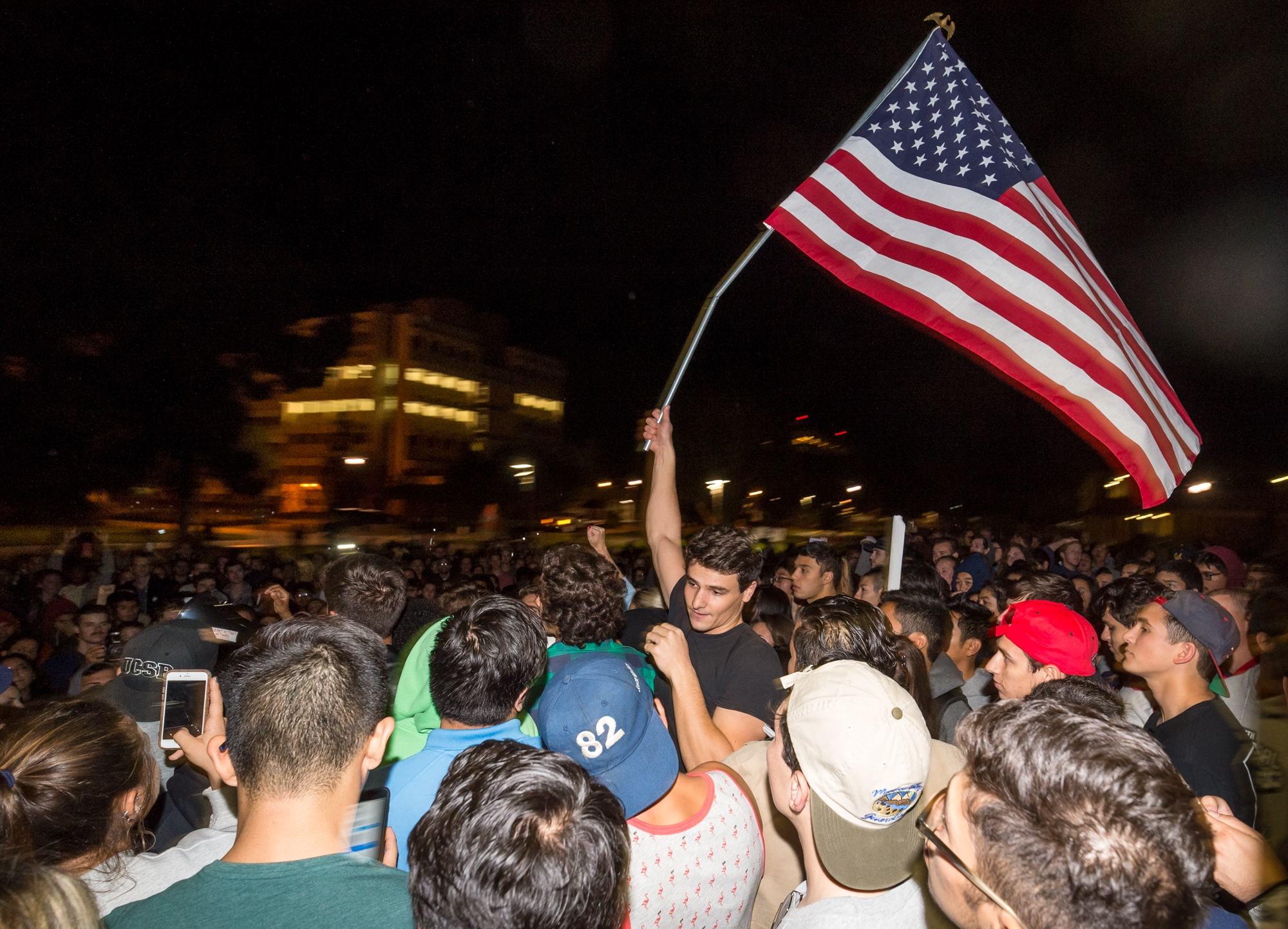 A Trump supporter waves a United States flag amidst a sea of students. Courtesy Kenneth Song
