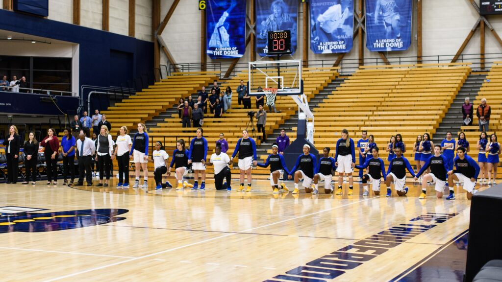 Many of the Gauchos women's Basketball team take a knee during the national anthem. Eric Swenson / Daily Nexus