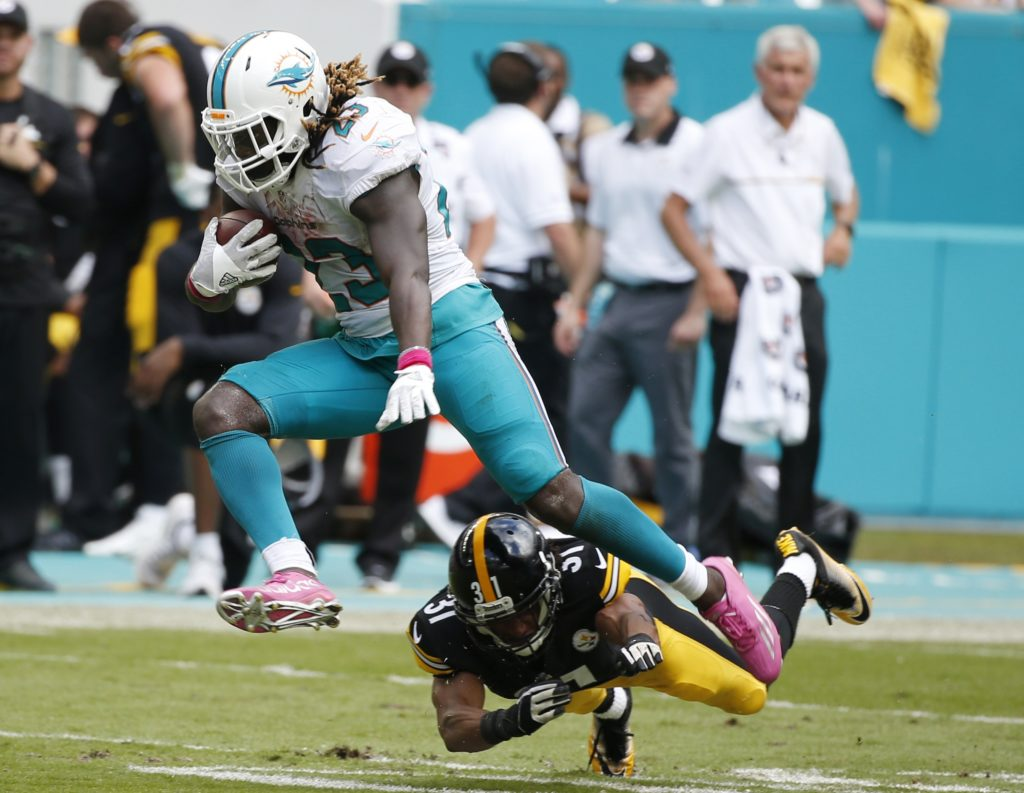 Miami Dolphins running back Jay Ajayi (23) avoids a tackle by Pittsburgh Steelers cornerback Ross Cockrell (31), during the second half of an NFL football game, Sunday, Oct. 16, 2016, in Miami Gardens, Fla. (AP Photo/Wilfredo Lee)